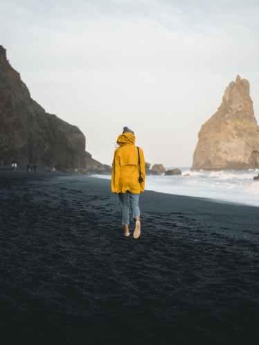 photo of person walking along seashore